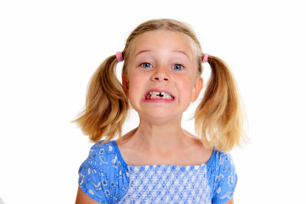 Young girl with pigtails missing teeth